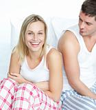 Smiling woman having fun with a man in bed