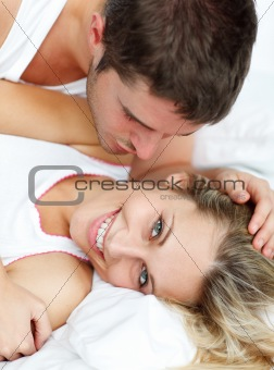 Man kissing his grilfriend in bed