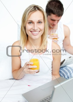 Couple drinking orange juice and reading news in bed
