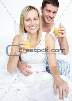 Boyfriend and girlfriend drinking orange juice in bed