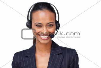 Beautiful ethnic businesswoman with a headset on smiling at the