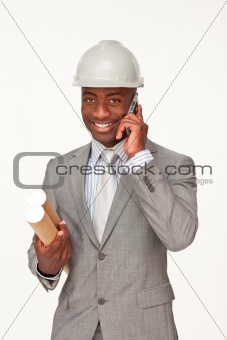 Attractive ethnic architect on phone holding plans