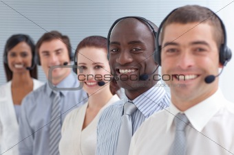 Afro-American businessman smiling and standing in a call center