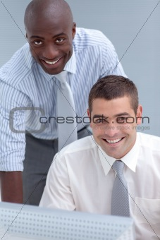 Two businessmen using a computer in office