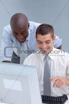 Caucasian and Afro-American businessmen using a laptop