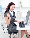 Businesswoman holding an apple in office