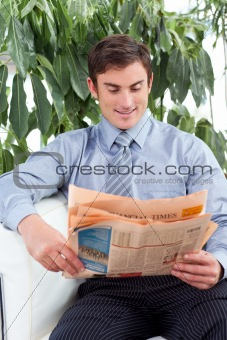 Attractive businessman reading a newspaper on a sofa