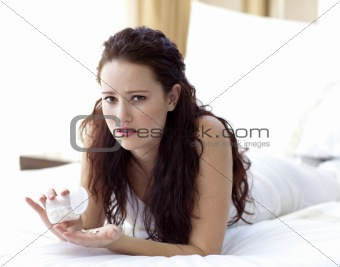 Concerned woman in bed taking pills