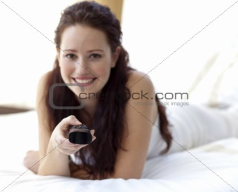 Beautiful woman in bed holding a remote