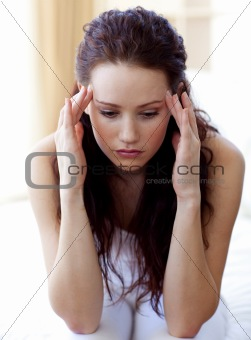 Beautiful woman having a headache in bed