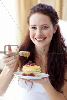 Smiling woman eating pancakes with fruit and honey