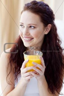 Portrait of woman drinking orange juice in bedroom