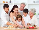 Parents, grandparents and children baking in the kitchen