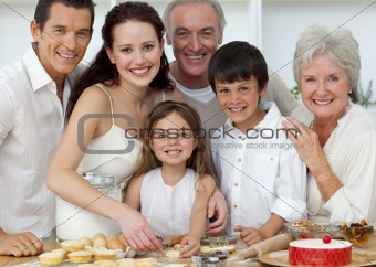 Portrait of parents, grandparents and children baking in the kit
