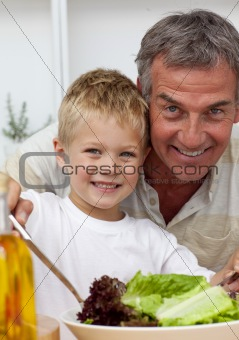 Happy grandfather cooking a salad with grandson