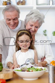 Happy grandparents eating a salad with granddaughter
