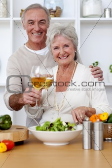 Happy senior couple eating a salad in the kitchen