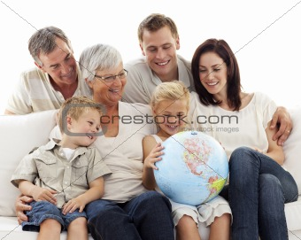Big family on sofa looking at a terrestrial globe