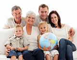 Big family on sofa holding a terrestrial globe