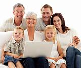 Smiling family using a laptop at home