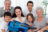 Portrait of family holding a guitar in living-room