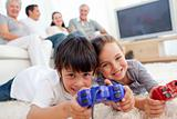 Children playing video games on floor and family on sofa