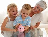 Grandmother and children saving money in a piggybank