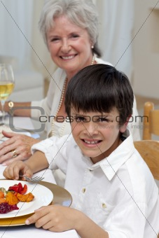 Smiling boy having dinner with his family