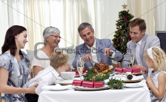 Family eating turkey in Christmas Eve