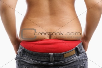 Back side of fat woman trying to wear tight jeans