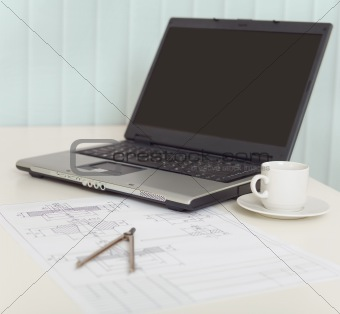 Business still-life from laptop, cups, drawing and compasses