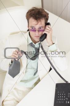 Young businessman speaks on phone, worries and rumples tie