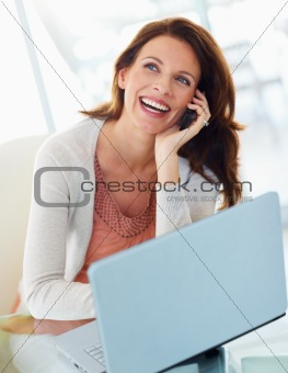 A cheerful woman using cellphone with laptop in front