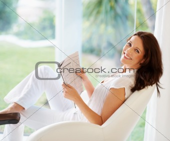 Portrait of a cheerful woman holding newspaper