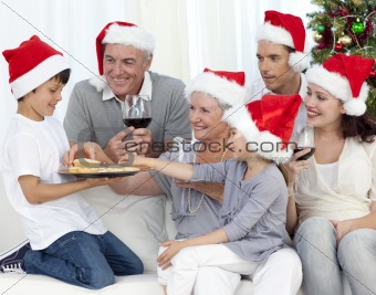 Family drinking wine and eating sweets in Christmas