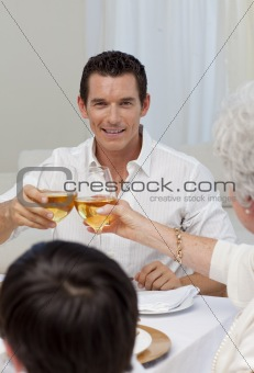 Attractive man toasting with his mother in a dinner