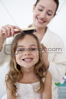 Portrait of mother doing her daughter's hair