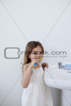 Little girl cleaning her teeth in bathroom with copy-space