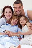 Smiling family playing in bed