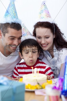 Little boy blowing out candles on his birthday's day