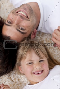 Portrait of father and daughter on floor with heads together