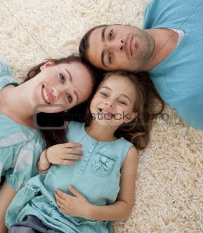 Portrait of parents and daughter on floor with heads together