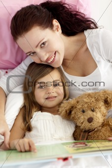 Portrait of mother and daughter reading in bed