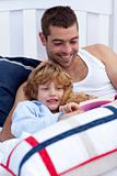 Father and son reading a book together in bed together