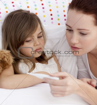 Portrait of mother taking her daughter's temperature