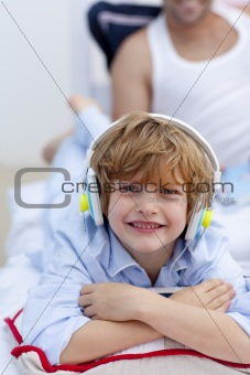 Little boy listening to music in bedroom