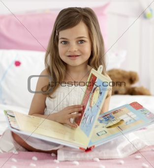 Beautiful little girl reading in bed