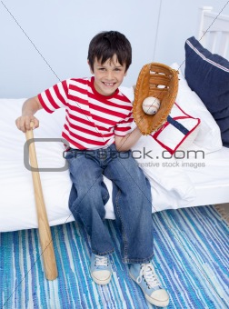 Little boy playing baseball in bed