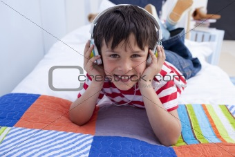 Boy relaxing in bed listening to music with headphones on
