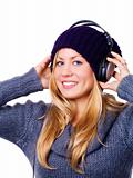smiling blond woman with headphones listening music over white